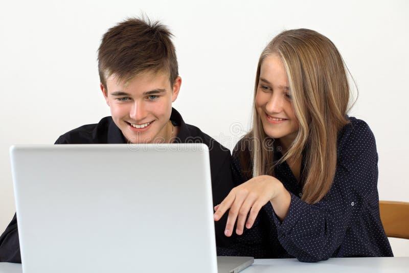 Estudantes novos que trabalham em um portátil fotografia de stock