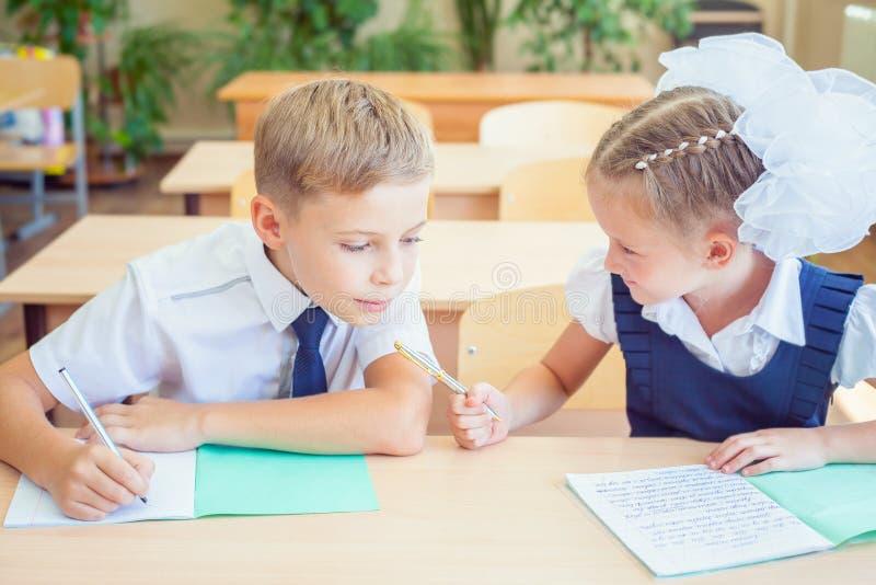 Estudantes ou colegas na sala de aula da escola que senta-se junto na mesa fotos de stock