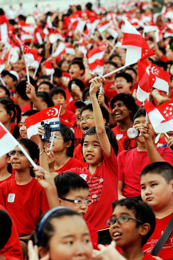 Estudantes que acenam bandeiras de Singapore durante NDP 2009 foto de stock