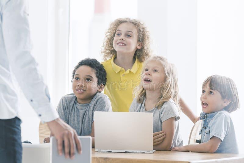 Estudantes que admiram o professor de ciências do computador fotos de stock royalty free