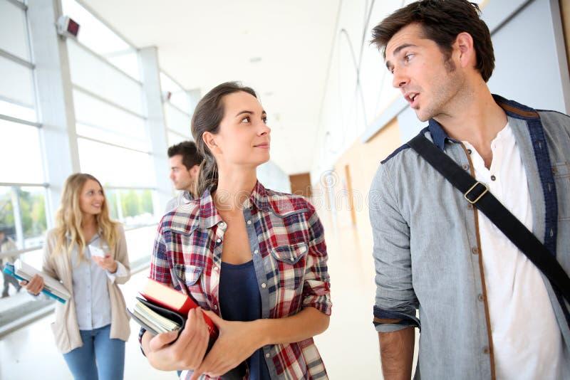 Estudantes que andam na fala do corredor imagens de stock royalty free