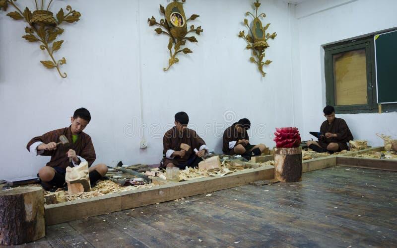 Estudantes que aprendem a cinzeladura butanesa tradicional da madeira fotos de stock