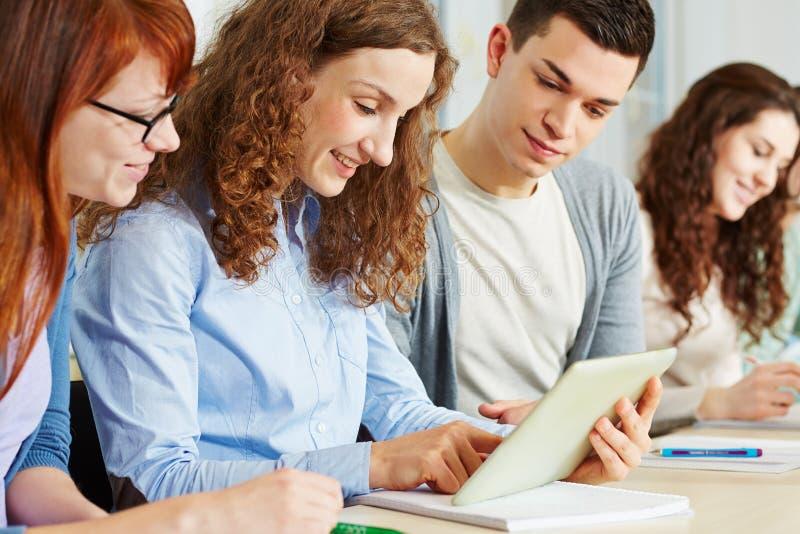 Estudantes em linha com tabuleta fotografia de stock royalty free