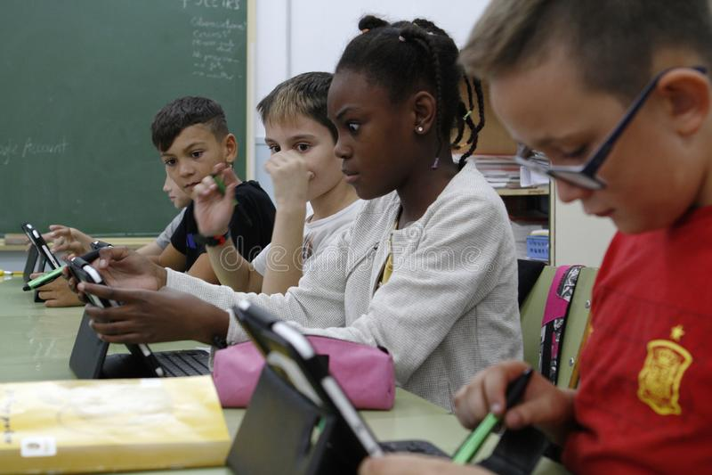Estudantes que aprendem os perigos e os bons usos do Internet e das redes sociais imagens de stock