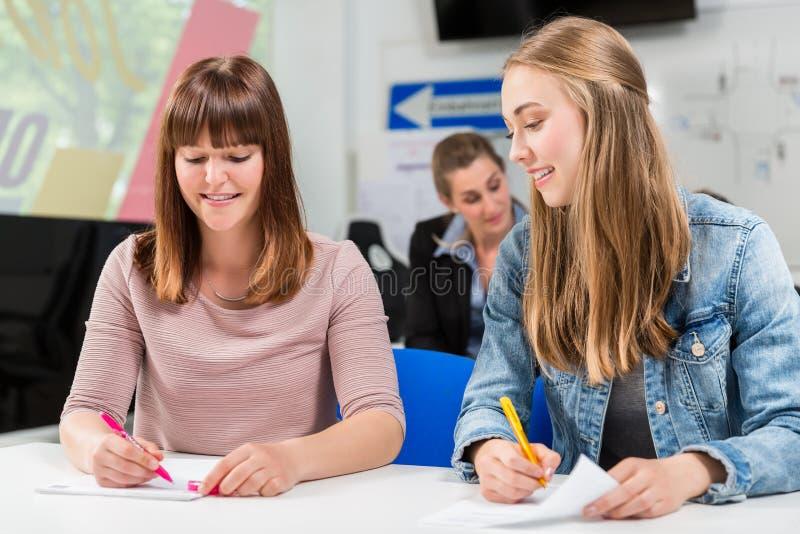 Estudantes que escrevem o teste ou o exame após ter terminado suas lições de condução imagens de stock royalty free