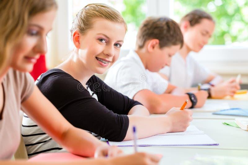 Estudantes que escrevem um teste na concentração da escola fotos de stock royalty free
