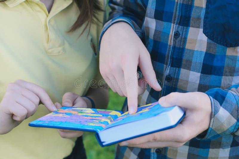 Estudantes que estudam para passar um exame Colegas que leem um livro imagens de stock royalty free