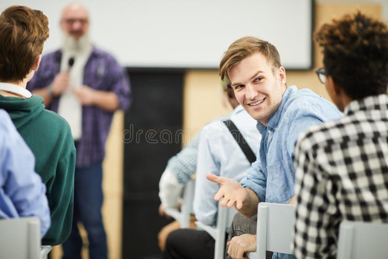 Estudantes que falam no auditório durante a conferência imagens de stock