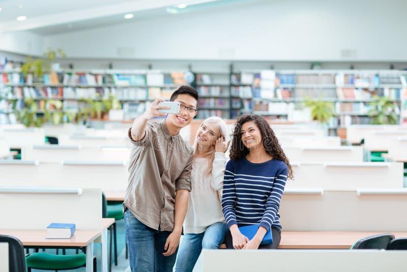 Estudantes que fazem a foto do selfie no smartphone na biblioteca fotografia de stock