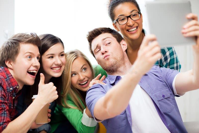 Estudantes que fazem a imagem com o PC da tabuleta na escola imagem de stock royalty free