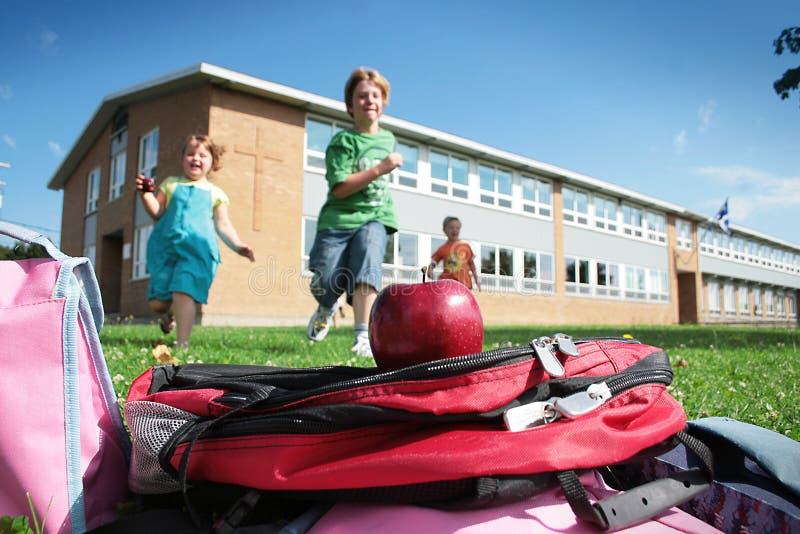Estudantes que funcionam ao saco de escola imagens de stock