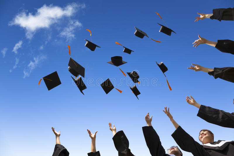 Estudantes que jogam chapéus da graduação imagem de stock royalty free