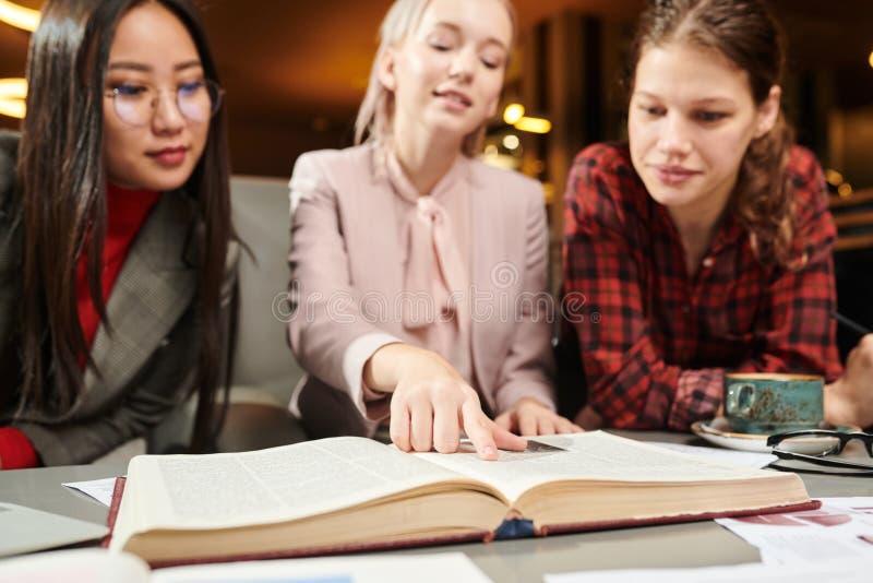 Estudantes que lêem um livro imagens de stock