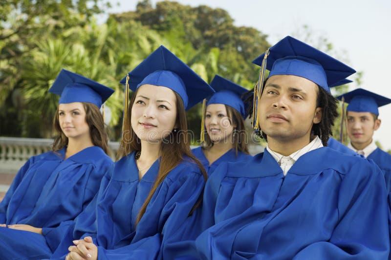 Estudantes que olham afastado durante a cerimônia de graduação fotos de stock