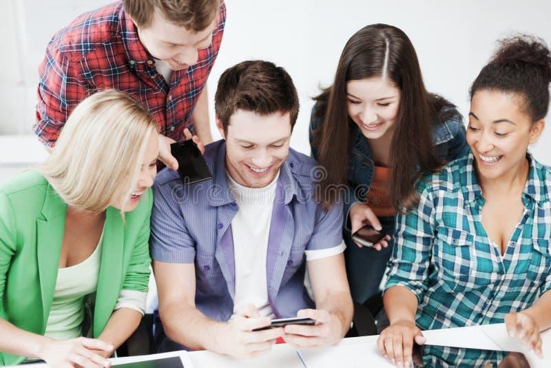 Estudantes que olham no smartphone na escola imagens de stock royalty free