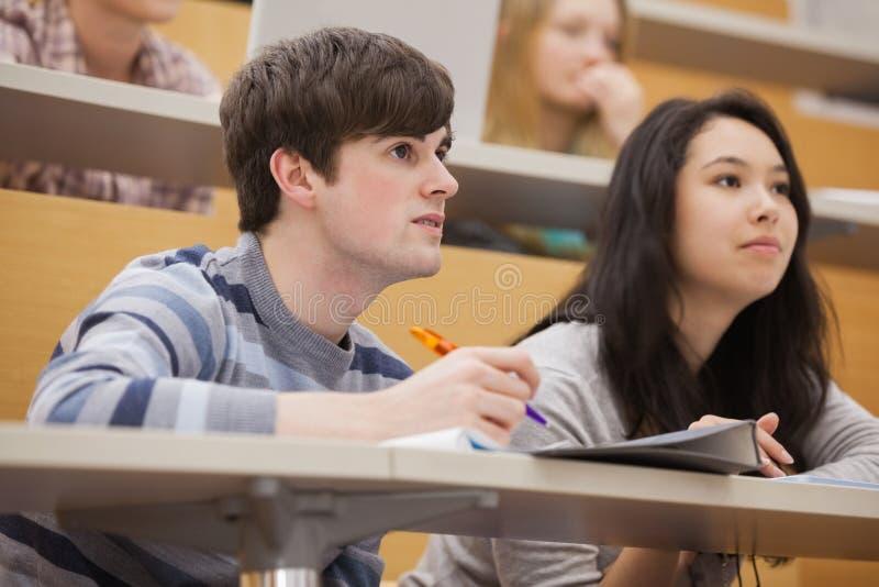 Estudantes que pagam a atenção ao sentar-se em um salão de leitura imagens de stock