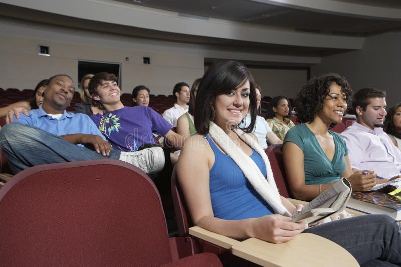Estudantes que sentam-se junto na sala de aula imagens de stock
