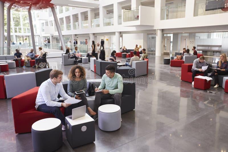 Estudantes que sentam-se no vestíbulo da universidade, três no primeiro plano fotografia de stock
