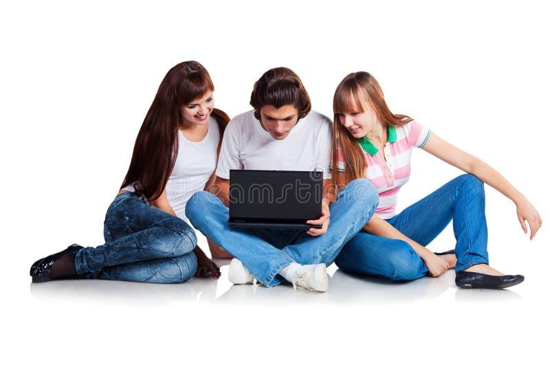 Estudantes que situam com portátil foto de stock royalty free