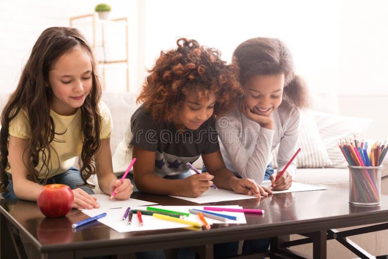 Estudantes que tiram com lápis coloridos em casa imagem de stock royalty free