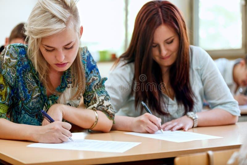 Estudantes que tomam o exame na universidade fotografia de stock