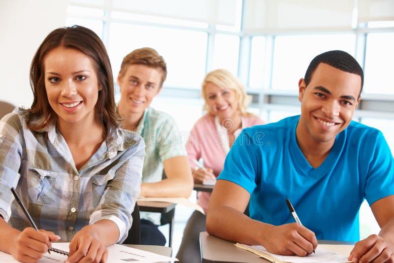 Estudantes que trabalham na sala de aula imagem de stock