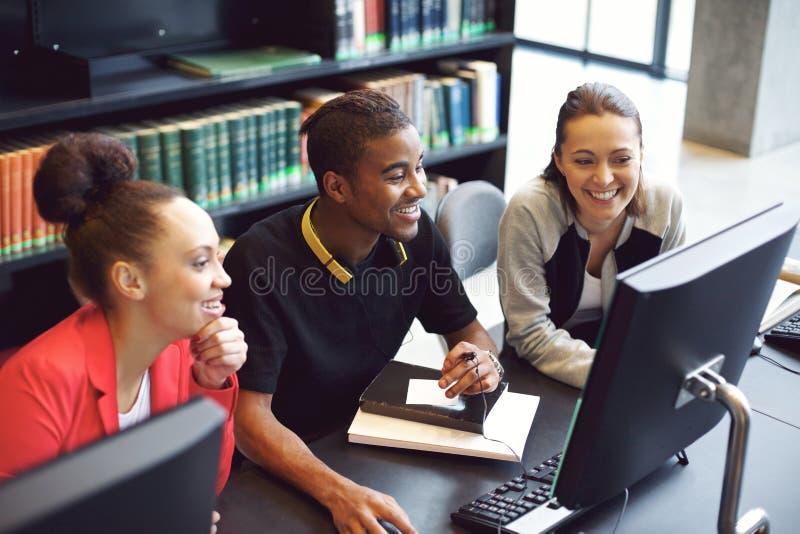 Estudantes que trabalham no computador em uma biblioteca de faculdade imagem de stock