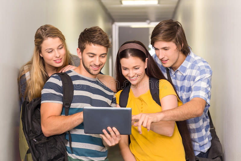Estudantes que usam a tabuleta digital no corredor da faculdade imagem de stock