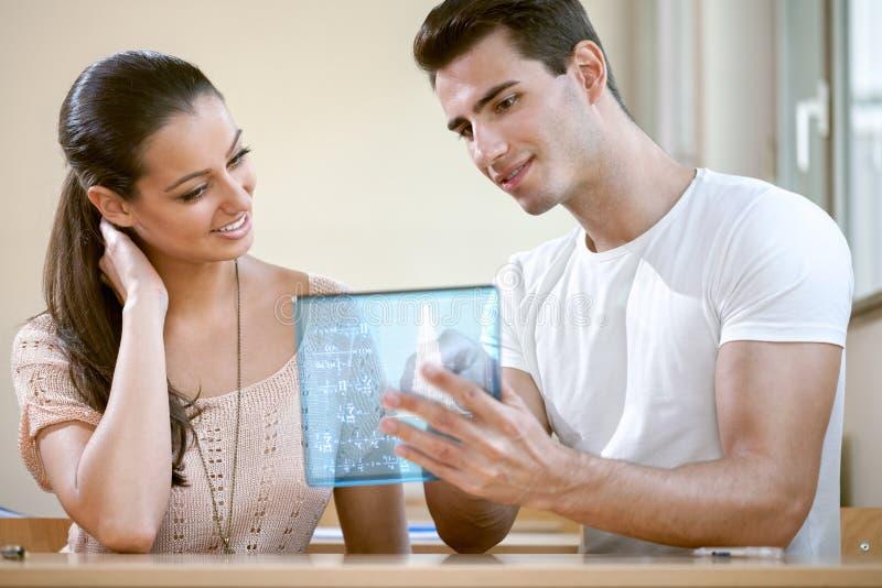 Estudantes que usam a tabuleta futurista foto de stock