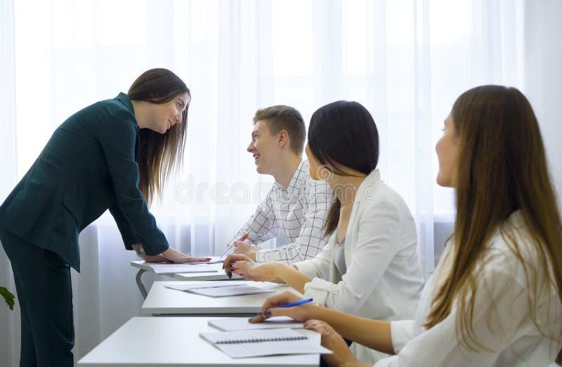 Estudantes universitário caucasianos novas conhecimento e habilidades do chek e do controle do professor na sala de aula imagem de stock