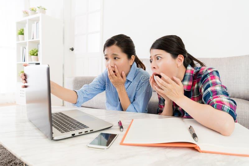 Estudantes universitário fêmeas novas que usam o portátil móvel fotos de stock