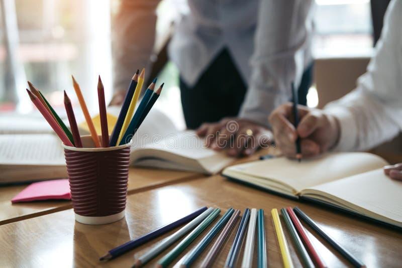 Estudantes universitário novas asiáticas que estudam junto o assento na mesa na biblioteca fotografia de stock