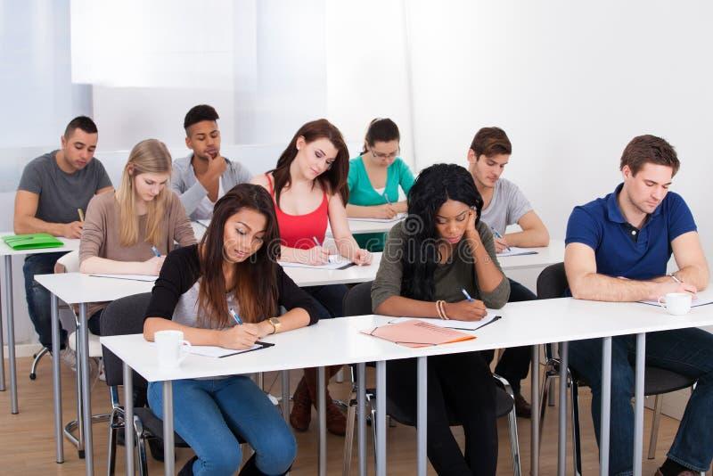 Estudantes universitário que escrevem na mesa fotos de stock