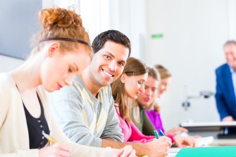 Estudantes universitário que escrevem o teste imagens de stock
