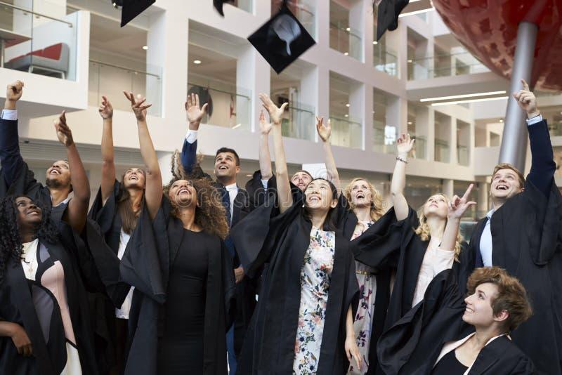 Estudantes universitário que jogam seus tampões no ar no dia de graduação imagem de stock