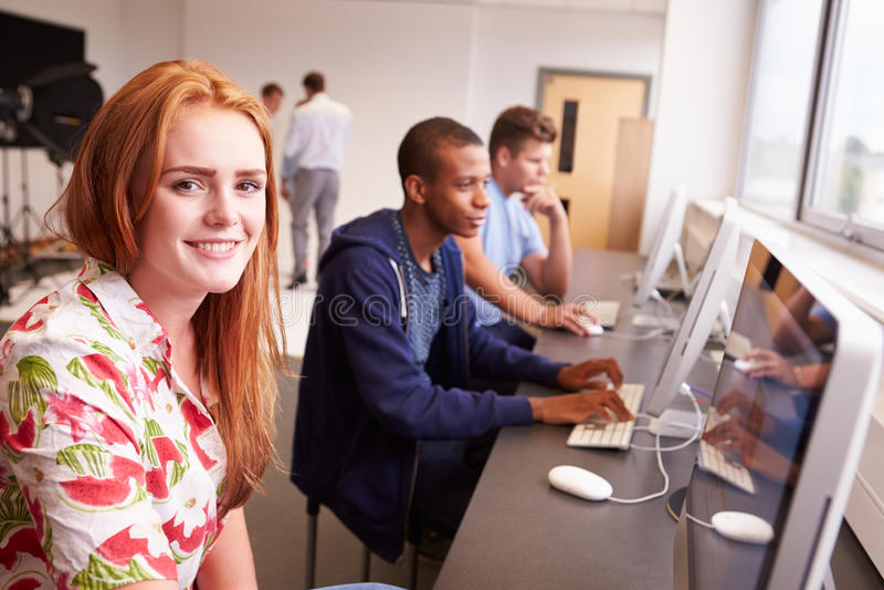 Estudantes universitário que usam computadores no curso de estudos dos meios imagens de stock