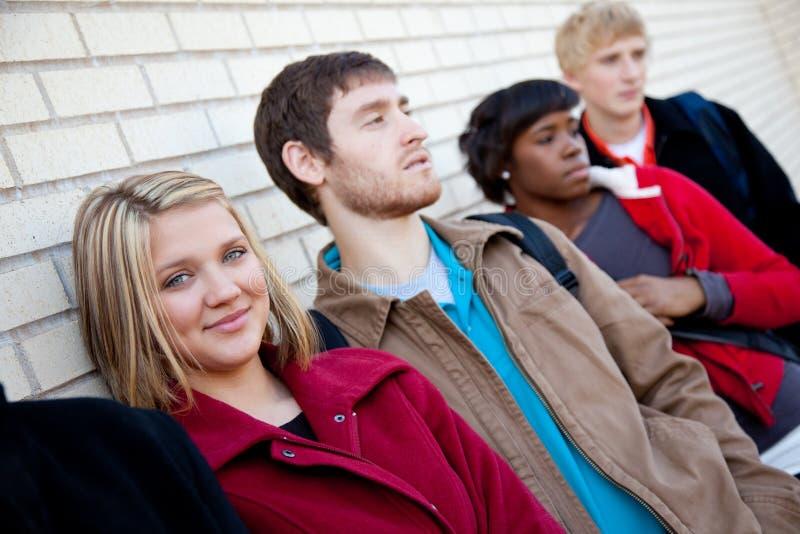 Estudantes universitários Multi-racial de encontro a uma parede de tijolo foto de stock royalty free