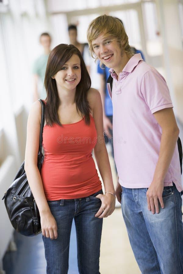 Estudantes universitários que estão no corredor da universidade imagens de stock royalty free