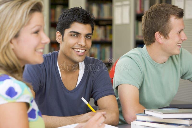 Estudantes universitários que estudam junto em uma biblioteca imagens de stock royalty free