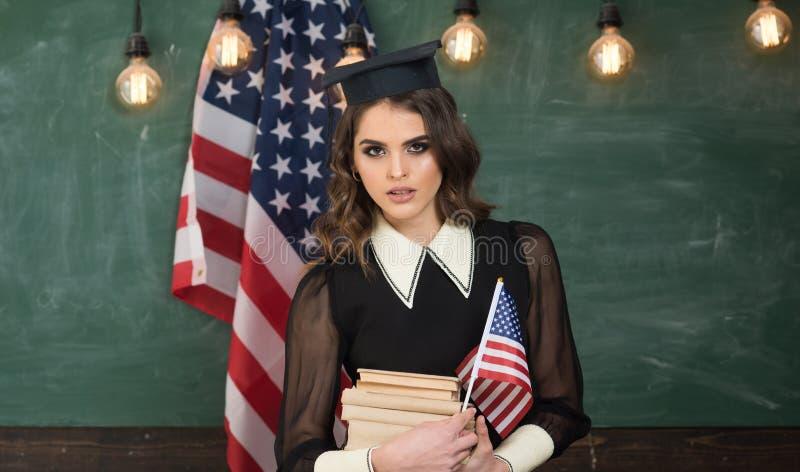 Estudantes universit?rio que gesticulam os polegares acima na biblioteca contra a bandeira dos EUA na tabela Aprendendo a l?ngua  imagem de stock royalty free