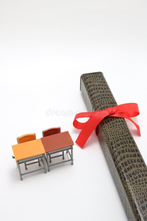 Estude mesas e diploma com uma fita vermelha no fundo branco fotos de stock