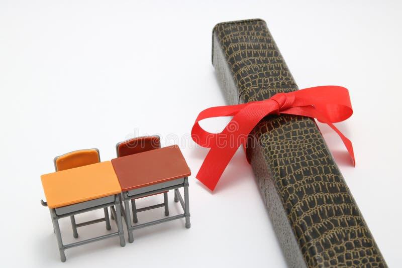 Estude mesas e diploma com uma fita vermelha no fundo branco fotos de stock royalty free
