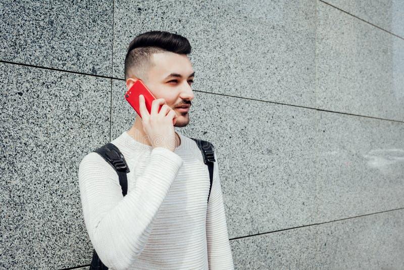 Estudiante árabe que llama a amigos afuera Groupmates que esperan sonrientes del hombre para después de clases fotografía de archivo libre de regalías