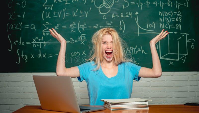 Estudiante aburrido que hace la preparaci?n en l?nea con un ordenador port?til Estudiante cansado de estudiar en sala de clase Hi imagen de archivo libre de regalías