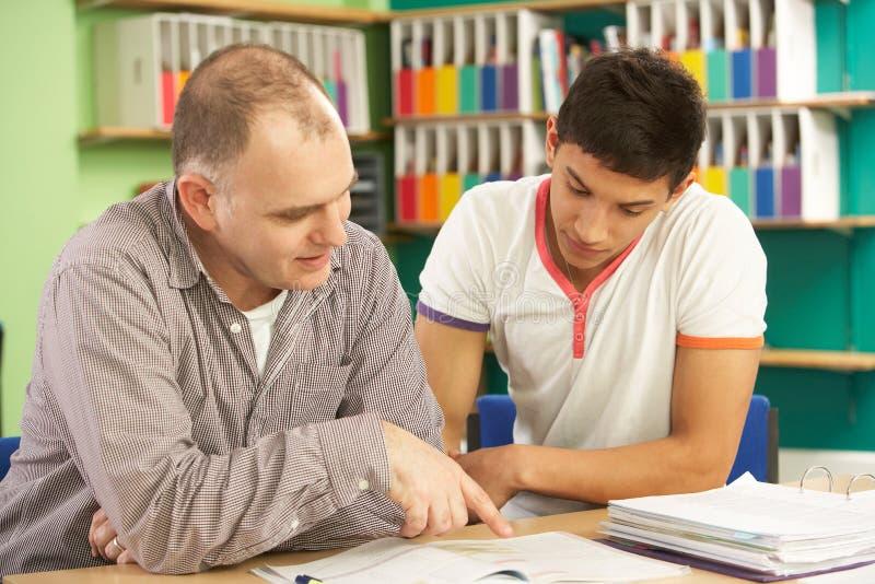 Estudiante adolescente en sala de clase con el profesor particular fotografía de archivo libre de regalías
