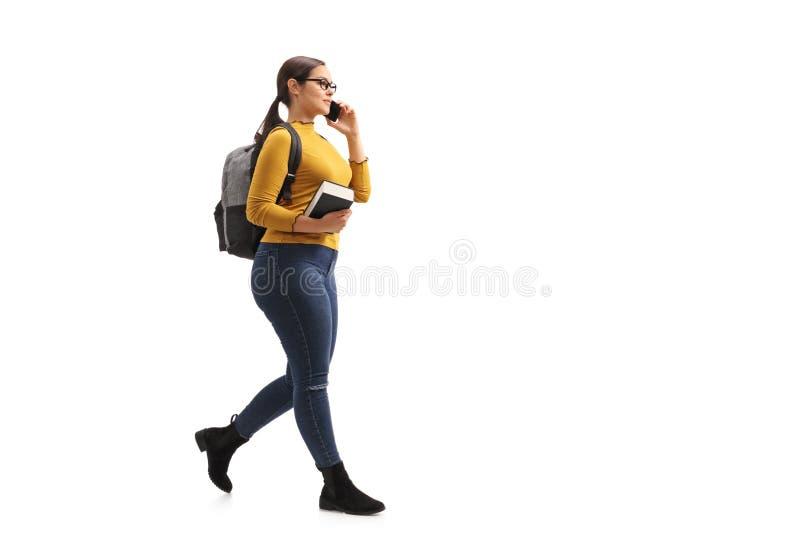 Estudiante adolescente femenino que camina y que habla en un teléfono imagenes de archivo