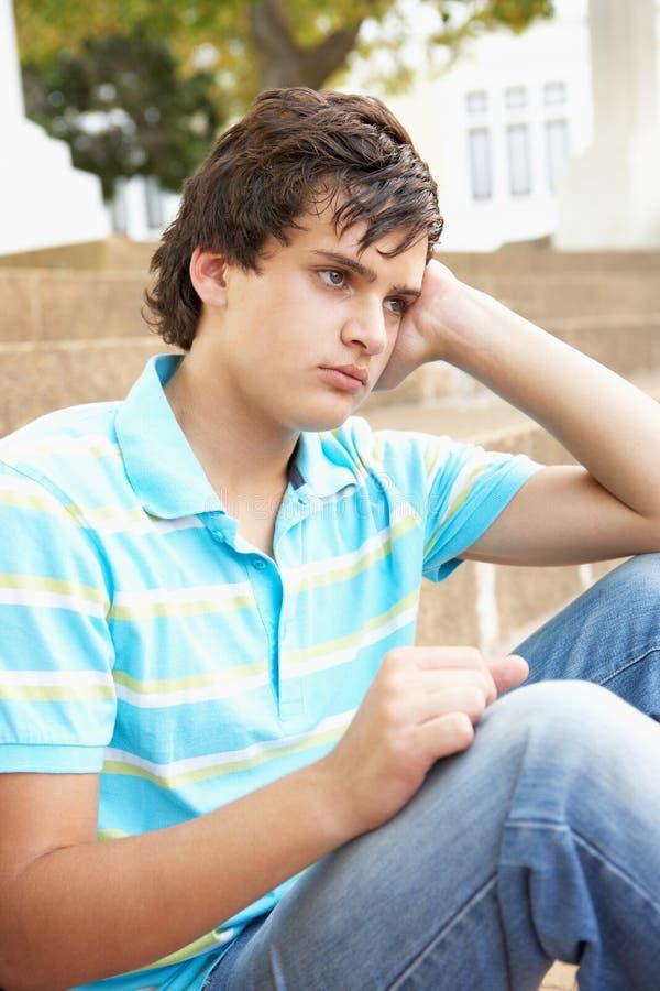 Estudiante adolescente masculino infeliz que se sienta afuera fotografía de archivo