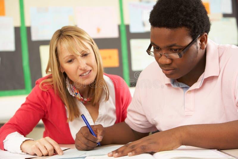 Estudiante adolescente masculino que estudia en sala de clase. foto de archivo