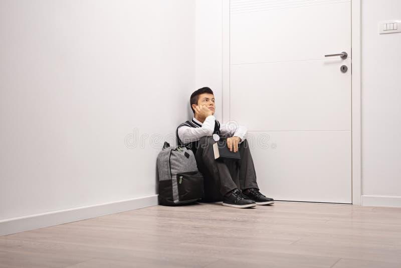 Estudiante adolescente pensativo que se sienta en una esquina dentro fotos de archivo