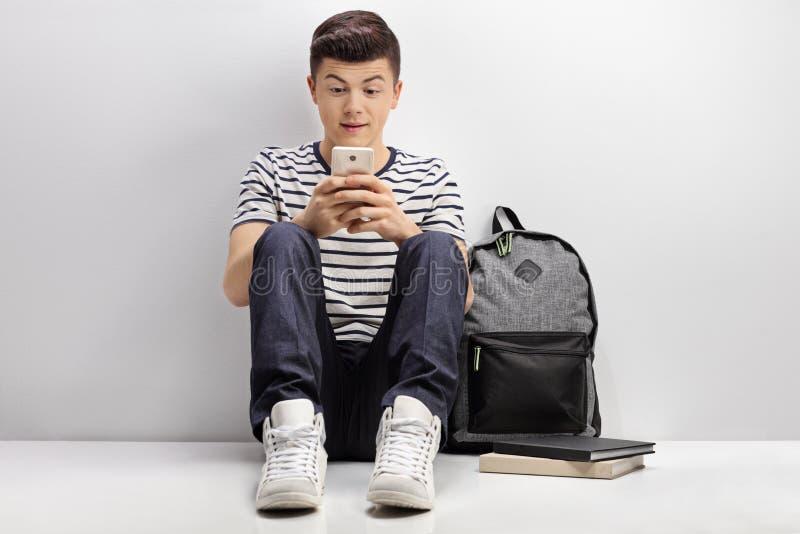 Estudiante adolescente que se inclina contra la pared blanca y que usa el teléfono foto de archivo libre de regalías